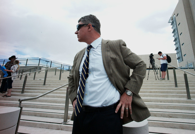 Attorney Mike Arnold, who represents Ammon Bundy, stands as people protest outside of the Lloyd George Federal Building ahead of an arraignment for Ammon and Ryan Bundy, among others, in Las Vegas ...