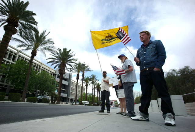 Steve, who declined to give his last name, left, and Michael Adams, right, protest with others outside of the Lloyd George Federal Building ahead of an arraignment for Ammon and Ryan Bundy, among  ...