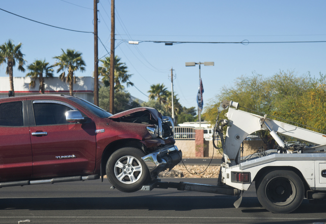 A truck that ran into the back of a school bus on U.S. Highway 95 is towed away from the scene down Boulder Highway in Las Vegas on Friday, April 1, 2016. Daniel Clark/Las Vegas Review-Journal Fol ...