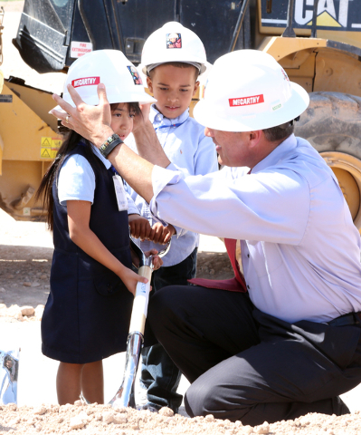 Nevada Gov. Brian Sandoval adjusts CT Sewell Elementary School student Gloria's hard hat as her schoolmate King, center, looks on Thursday, April 14, 2016 during the groundbreaking ceremony at the ...