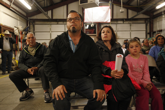 Stephen Rubyor, from left, his wife Crystal, and their daughter Isabella listen during a packed Town Hall meeting at the Volunteer Fire Department building in Mount Charleston Thursday, March 31,  ...