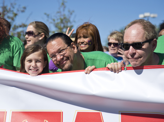 Penn Jillette, center, his daughter Moxie, left, and Teller stand at the starting line for the 26th annual Aid for AIDS of Nevada (AFAN) AIDS Walk Las Vegas at Town Square in Las Vegas on Sunday,  ...