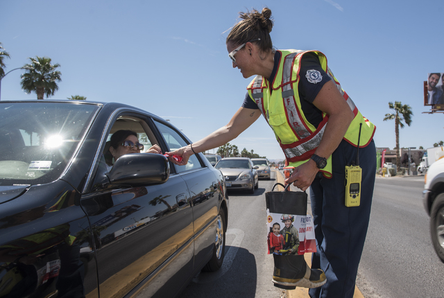 "Firefighter Mari Bussio, collects donations from motorists for the annual ""Fill the Boot"" drive that benefits the Muscular Dystrophy Association (MDA) at the corner or Sahara Ave ..."