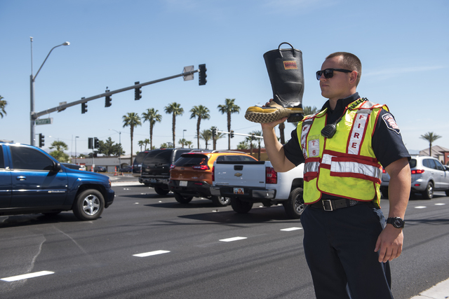 "Probation firefighter Collin Wick, greets motorists to collect donations for the annual ""Fill the Boot"" drive that benefits the Muscular Dystrophy Association (MDA) at the corner ..."
