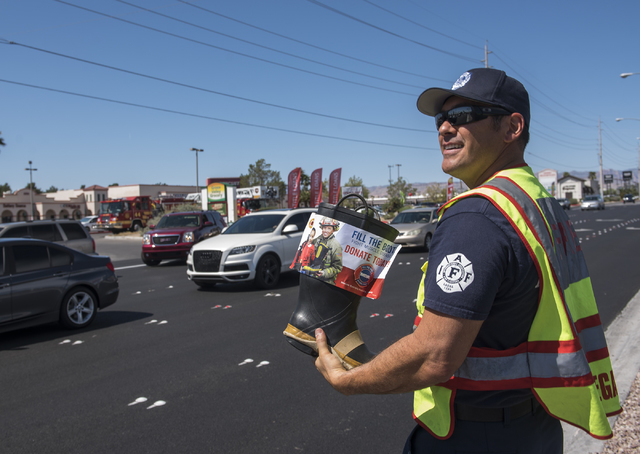 """Fire Engineer Kurt Bacca, greets motorists to collect donations for the annual """"Fill the Boot"""" drive that benefits the Muscular Dystrophy Association (MDA) at the corner or Sahar ..."""