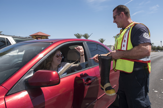 """Firefighter Paramedic Daniel Wolfe, collects donations from motorists for the annual """"Fill the Boot"""" drive that benefits the Muscular Dystrophy Association (MDA) at the corner or ..."""