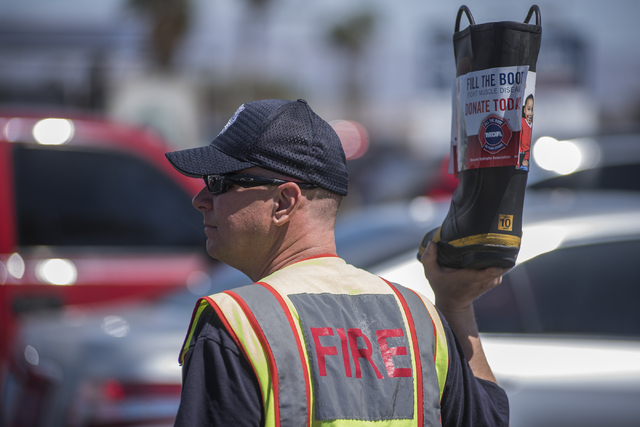"""Captain John Hurley, of Firestation 44, greets motorists to collect donations for the annual """"Fill the Boot"""" drive that benefits the Muscular Dystrophy Association (MDA) at the c ..."""