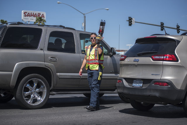 """Firefighter Mari Bussio, greets motorists to collect donations for the annual """"Fill the Boot"""" drive that benefits the Muscular Dystrophy Association (MDA) at the corner or Sahara ..."""