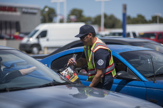 """Fire Engineer Kurt Bacca, collects donations from motorists for the annual """"Fill the Boot"""" drive that benefits the Muscular Dystrophy Association (MDA) at the corner or Sahara Av ..."""