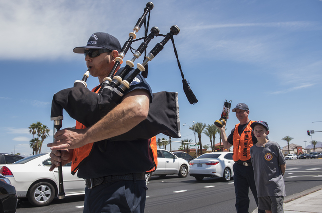 Fire Engineer Bill Caswell, left, plays the bagpipes as Firefighter Paramedic Ron Kline and MDA Goodwill Ambassador Jake Roszelle greet motorists while collecting donations for the annual &quo ...