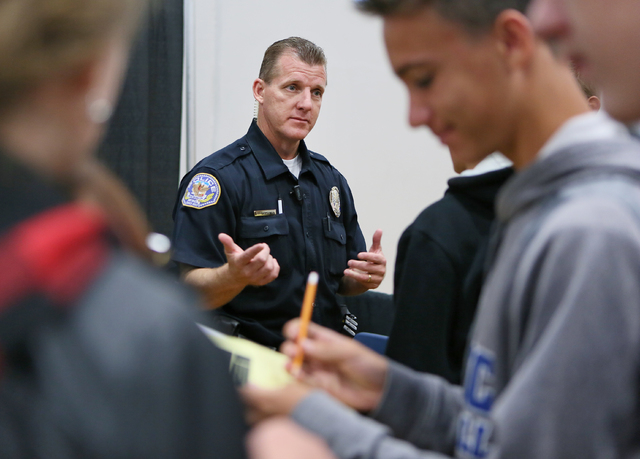 """Henderson Police officer Kenneth """"Zane"""" Simpson talks to freshmen about his job during the Integrating Career Academies by Networking Business and Education program at Basic High ..."""