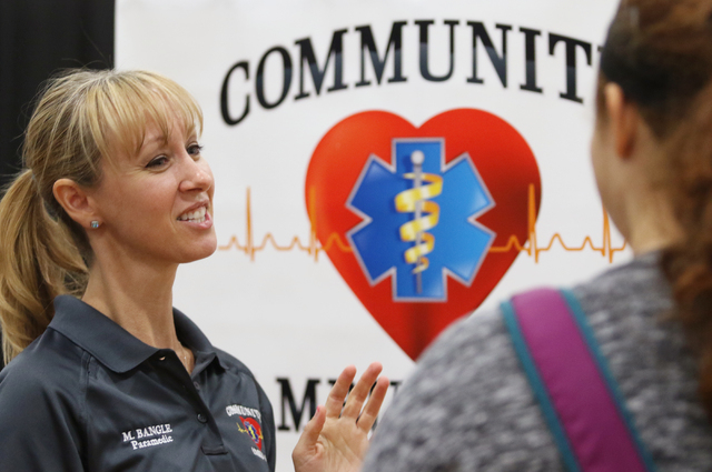 Community Ambulance paramedic Melanie Bangle, left, talks to freshmen about her job during the Integrating Career Academies by Networking Business and Education program at Basic High School Wednes ...