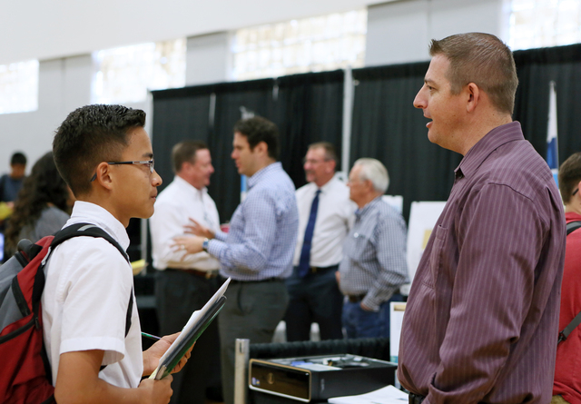 Hunter Espaniola, left, visits with Stimulus Technologies' system engineer Kaid Whipple at an information technologies booth during the Integrating Career Academies by Networking Business and Educ ...