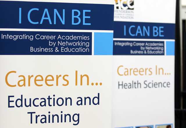 Posters are shown at booths during the Integrating Career Academies by Networking Business and Education program at Basic High School Wednesday, April 20, 2016, in Henderson. Students visited boot ...
