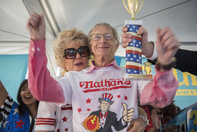 Henderson couple Carlene LeFevre, left, supports her husband Rich as he is presented with the men's championship trophy after winning the Nathan's Famous Hot Dog Eating Contest qualifier with 30 h ...