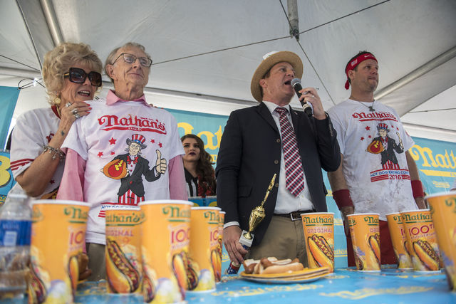 Carlene LeFevre, from left, stands behind her husband, Rich LeFevre, as host Sam Barclay introduces him as the winner of the men's Nathan's Famous Hot Dog Eating Contest qualifier at the Brooklyn  ...