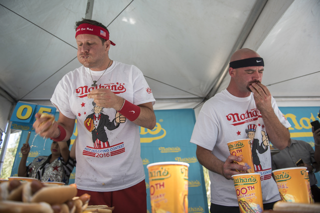 Professional eaters, from left, Eric Denmark and Steve Hendry compete during the Nathan's Famous Hot Dog Eating Contest qualifier from the Brooklyn Bridge at New York-New York hotel-casino in Las  ...