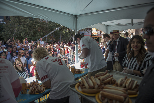 The crowd cheers on the competitors during the Nathan's Famous Hot Dog Eating Contest qualifier at the Brooklyn Bridge at New York-New York hotel-casino in Las Vegas on Saturday, April 23, 2016. M ...