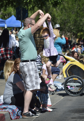 Avery Vidrine, right, gets a lift from her father Nathan while dancing to the music of a marching band during the Henderson Heritage Parade and Festival in downtown Henderson on Saturday, April 23 ...