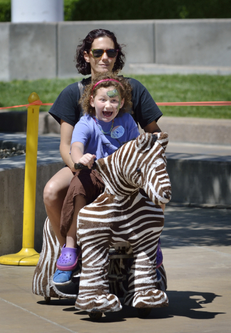 Star Arasmith, front, rides a Zippy Pal with her mother Wednesday during the Henderson Heritage Parade and Festival in downtown Henderson on Saturday, April 23, 2016. (Bill Hughes/Las Vegas Review ...
