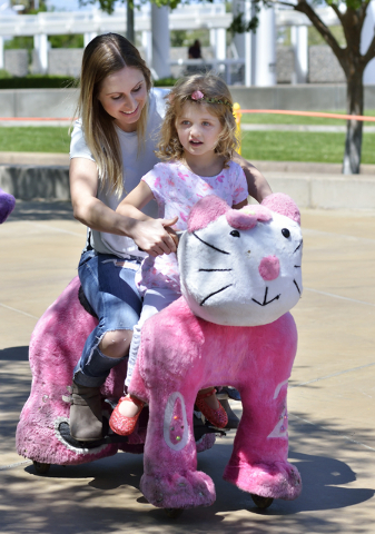 Tiffany Cooper, left, takes a ride on a Zippy Pal with her daughter Faith during the Henderson Heritage Parade and Festival in downtown Henderson on Saturday, April 23, 2016. (Bill Hughes/Las Vega ...
