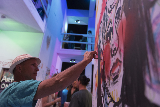 Curtis Sill paints during the illumination ceremony for the Life Cube in the Llama Lot at Fremont Street and 9th Street in Las Vegas Saturday, March 19, 2016. The ceremony kicks off two weeks of c ...