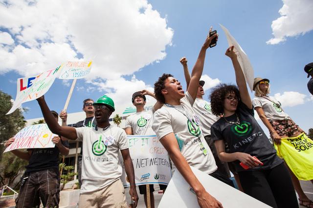 Solar energy supporters Joshua Chappell, left, Alex Wenzel and Unika Osborne protest outside NV Energy, April 22, 2015. (Chase Stevens/Las Vegas Review-Journal Follow  @csstevensphoto)