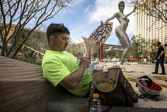 Construction worker Steve Gonzales takes lunch break near the Bliss Dance sculpture created by  Marco Cochrane during an unveiling at The Park, MGM Resorts InternationalÕs outdoor dining and ente ...