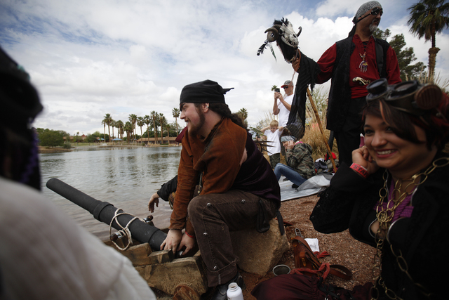 A gentleman who declined to be named shoots a fake cannon at the beginning of a boat's race as Sebia Rice, right, holds her ears, at the Cardboard Regatta at the Pirate Fest at Lorenzi Park in Las ...