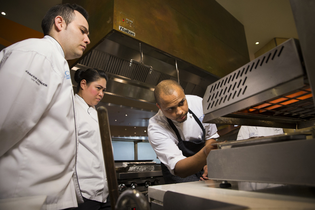 Sean Mackey, right, a participant in the Culinary Associates Program, checks on the status of his salmon dish at the Aria Resort & Casino, Tuesday, April 19, 2016, in Las Vegas. Candidates can ...