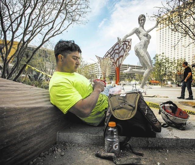 Construction worker Steve Gonzales takes lunch break near the Bliss Dance sculpture created by  Marco Cochrane during an unveiling at The Park, MGM Resorts Internationalճ outdoor dining and  ...