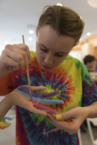 15-year-old Saylor Helms paints 16-year-old Caroline Cohen's hand during a collaborative art project, at Yiddish Las Vegas: A Music & Culture Festival at Temple Sinai in Las Vegas Sunday, Apri ...