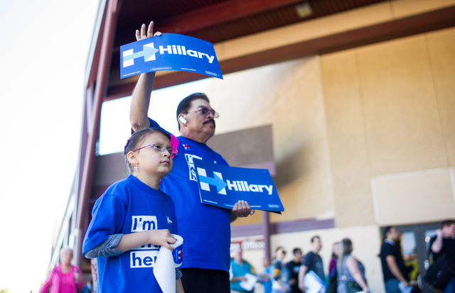 Jose Mejia and daughter Kayla, 7, hand out signs and stickers to supporters of Democratic presidential candidate Hillary Clinton at the Clark County Democratic Party Convention at Cashman Center i ...
