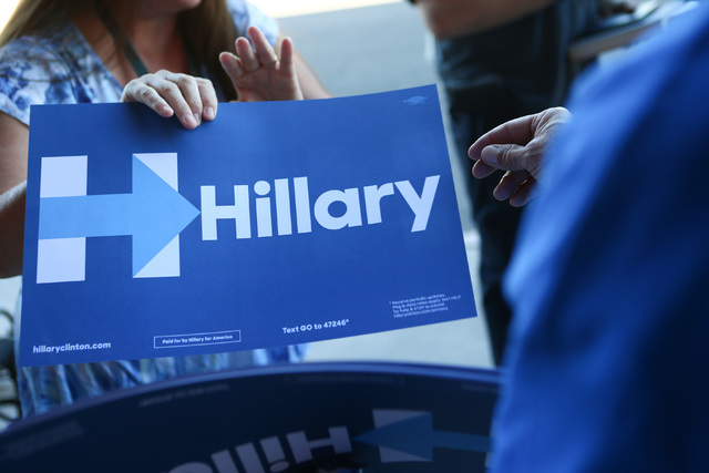 Jose Mejia gives a sign to a supporter of Democratic presidential candidate Hillary Clinton at the Clark County Democratic Party Convention at Cashman Center in Las Vegas on Saturday, April 2, 201 ...