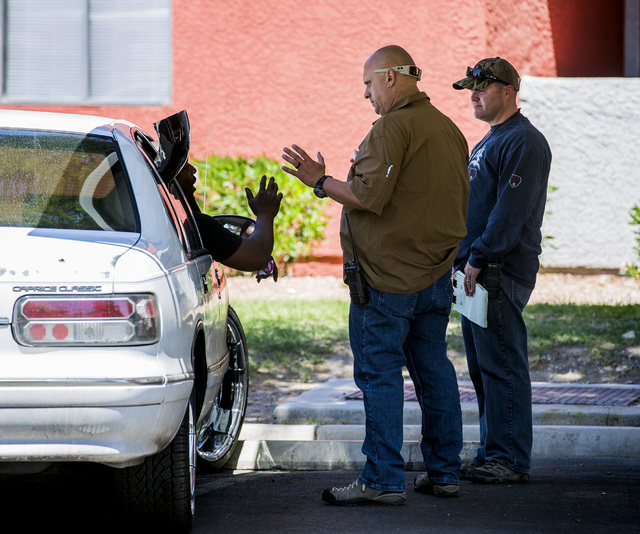 Officers Damian Walburn, center, and Blaine Martell, right, with Metro's Targeting Neighborhood Taggers talks to a man while investigating in the Liberty Village Apartment complex on Tuesday, Apri ...
