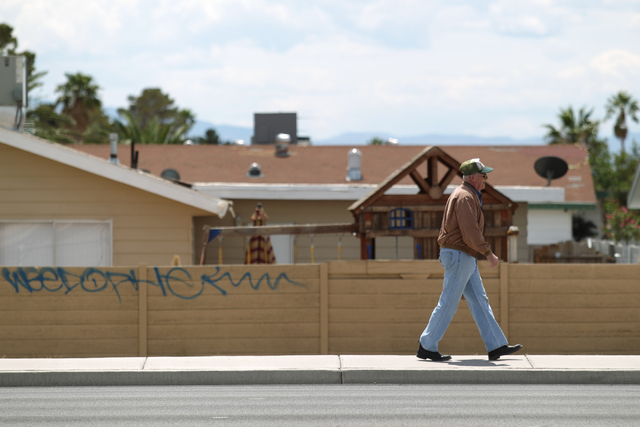 A pedestrian walks past graffiti on the backyard wall of home on East Craig Road in Las Vegas on Friday, April 29, 2016.  (Brett Le Blanc/Las Vegas Review-Journal) Follow @bleblancphoto