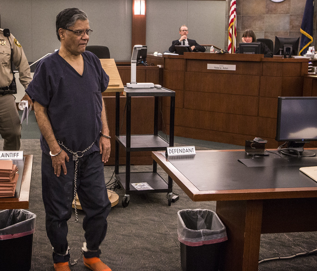 A shackled Dr. Dipak Desai is escorted out of court after District Judge Valerie Adair sentenced him to life in prison with the possibility of parole after 18 years, Thursday, Oct. 24, 2013, at th ...