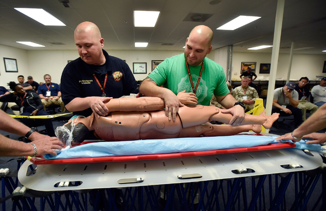 "Ben Snodgrass, left, of the Bentonville, Ark., Fire Department and Alex Ralls-Novo of Orlando, Fla., Fire-Rescue assist with a ""victim"" during an exercise at the Nevada National Security Site on W ..."