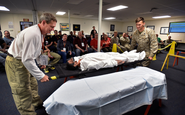 "John Scheurigh, left, of the Chicago Fire Department and Marine Sgt. Jeremy Price assist with a ""victim"" during a decontamination exercise at the Counter-Terrorism Operations Support at the Nevada ..."