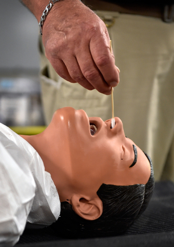 "Robb Pilkington demonstrates taking a nasal sample from a ""victim"" during a decontamination exercise at the Counter-Terrorism Operations Support at the Nevada National Security Site on Wednesday,  ..."