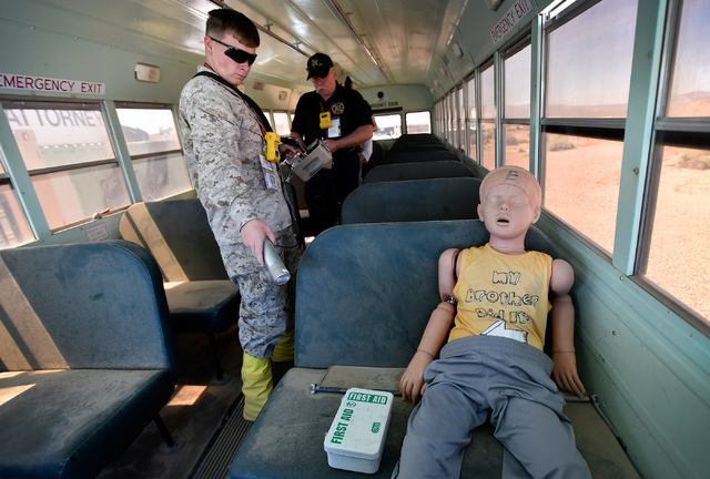 "Marine Michael Seabold surveys for radioactive material near a ""victim"" inside a bus at the Counter-Terrorism Operations Support training facility  at the Nevada National Security Site on Wednesda ..."