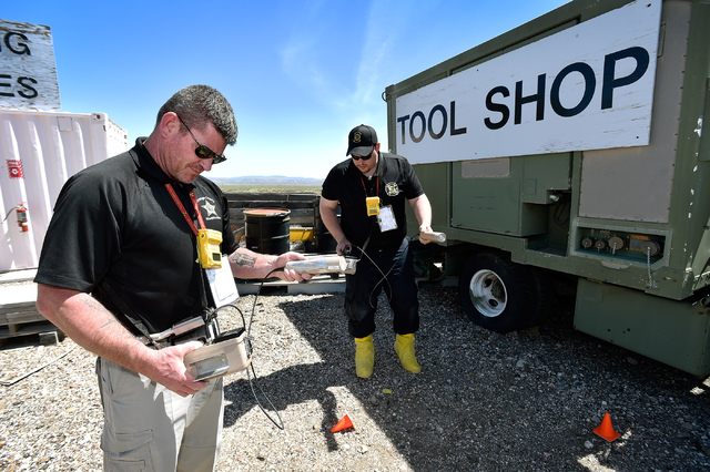 Troy Williams, left, with the Orange City, N.C., sheriff's office and Keith Weber of the Greenwood Forrest, N.J., Fire Company survey for radioactive material at the Nevada National Security Site  ...