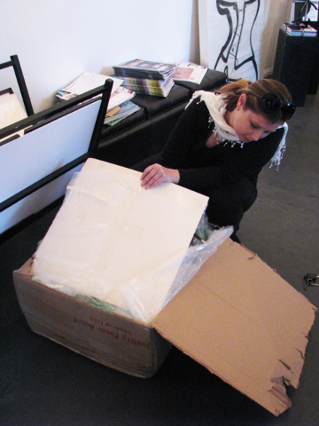 Laura Henkel, owner and curator of Sin City Gallery, unpacks a photo by Raymond Elstad March 24. F. Andrew Taylor/View
