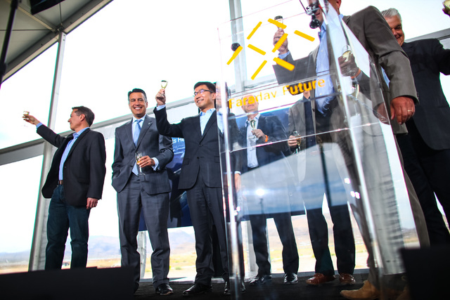 Faraday Future Vice President of Supply Chain Tom Wessner, from left, Gov. Brian Sandoval, and Ding Lei, co-founder and global vice chairman of SEE Plan, hold glasses of champagne during the groun ...