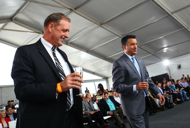 North Las Vegas Mayor John Lee, left, and Gov. Brian Sandoval hold glasses of champagne during the groundbreaking for Faraday Future's planned 900-acre manufacturing site in North Las Vegas on Wed ...