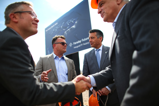 Faraday Future Vice President of Manufacturing Dag Reckhorn, center left, and Gov. Brian Sandoval speak with each other following the groundbreaking for Faraday Future's planned 900-acre manufactu ...