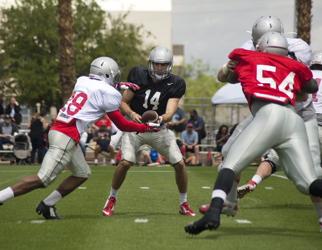 Quarterback Kurt Palandech (14) hands the ball to Keith Whitely (28) during the Spring Showcase football event at Peter Johann Memorial Field on the UNLV campus in Las Vegas on Saturday, April 9,  ...