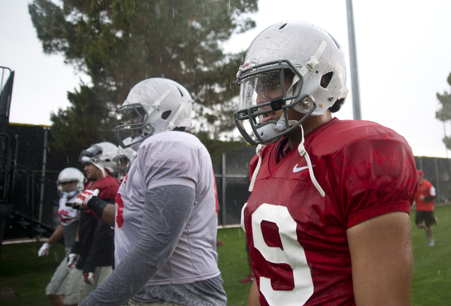 Mark Finau (19), right, walks off the field in the rain after the Spring Showcase football event at Peter Johann Memorial Field on the UNLV campus in Las Vegas on Saturday, April 9, 2016. The even ...