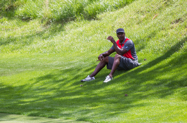 Michael Jordan relaxes in the shade on the fairway of the 8th hole during the Michael Jordan Celebrity Invitational at Shadow Creek Golf Course in North Las Vegas on Saturday, April 5, 2014. (Chas ...