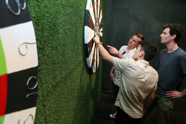 Brandon DeLaroche, front center, Ryan Viggiano, back left, and Bo Wolfe tally up points while playing darts at Gold Spike Tuesday, March 22, 2016, in Las Vegas. Gold Spike, with new design and own ...